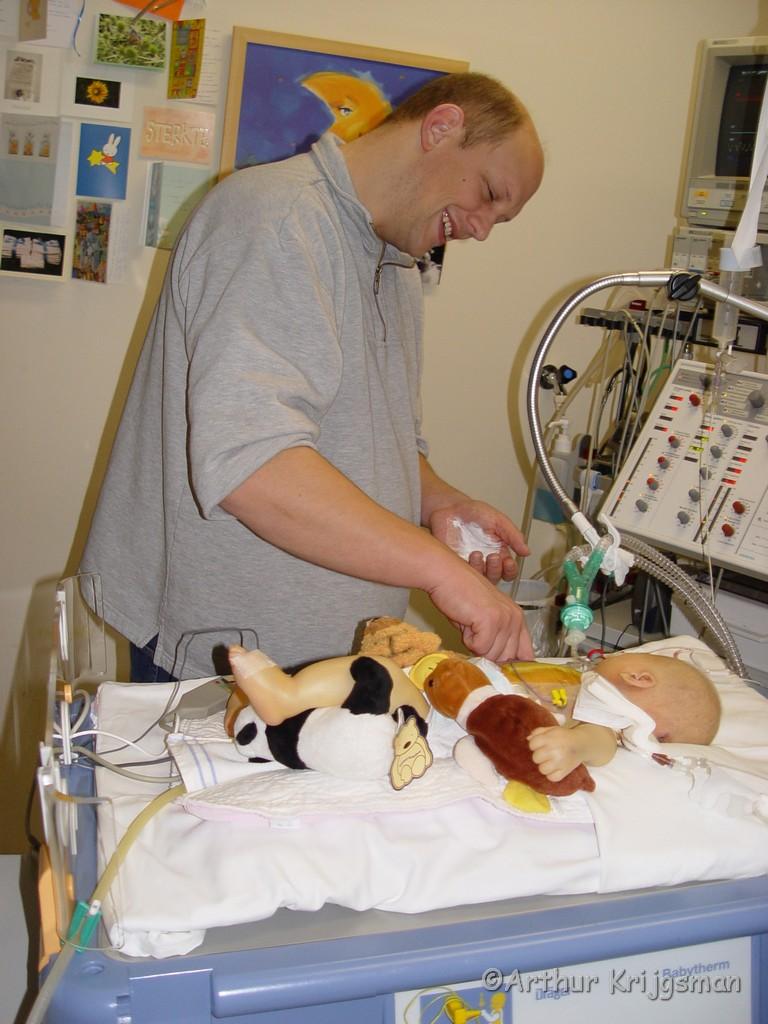 Papa verzorgt zieke kind in ziekenhuis.